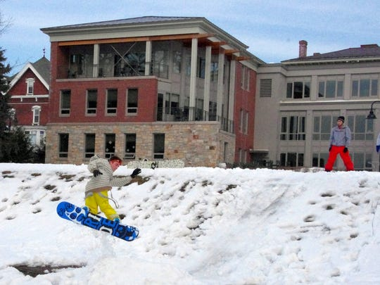 In 2011, Champlain College freshmen Ryan Terry of New Jersey (yellow pants) and Steve Sarkisian of Massachusetts practice their snowboard jumps and spins on campus.