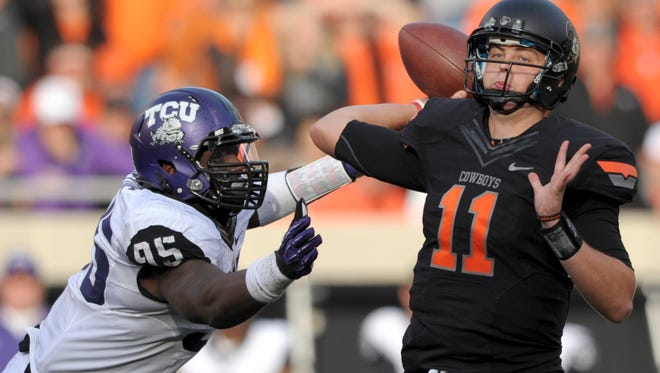 In this Oct. 27, 2012, file photo, TCU defensive end Devonte Fields, left, pressures Oklahoma State quarterback Wes Lunt, right, during an NCAA college football game in Stillwater, Okla. Fields was selected as the AP's Big 12 defensive player of the year, Wednesday, Dec. 5, 2012.