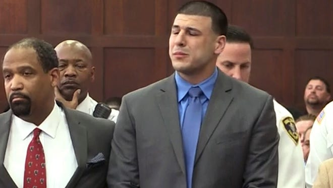 In this still image from video, Aaron Hernandez, right, listens beside defense attorney Ronald Sullivan, Friday, April 14, 2017, in court in Boston, as he is pronounced not guilty of murder in the 2012 shootings of two men in a drive-by shooting in Boston.