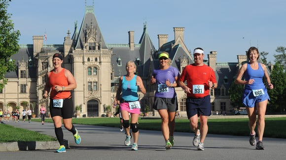 Participants in the Biltmore/Kiwanis 15K Classic run past the Biltmore House in a past race. The 20th annual race is May 21.