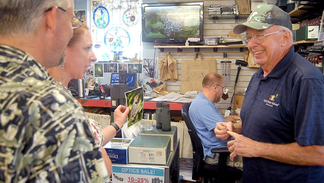 Tacoma resident Joel Bartsma, left, shares a laugh with WildBirds Unlimited owner Jim Ullrich as Colette Bartsma asks Ullrich about a photo of a bird on display on Monday, Aug. 28. New co-owner Greg Cole (seated) works at the store's paperwork files. Cole said he and his wife, Kecia, will share time between Gig Harbor and their currently owned WBU store in Puyallup.
