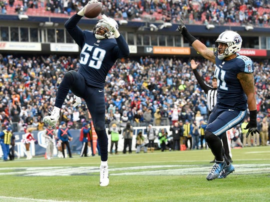 Titans linebacker Wesley Woodyard (59) scoops up the fumble by Rams quarterback Jared Goff (16) and scores a touchdown as linebacker Derrick Morgan (91) celebrates during the second quarter at Nissan Stadium Sunday, Dec. 24, 2017 in Nashville, Tenn.