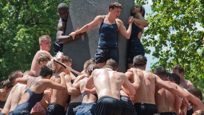 Midshipmen of the class of 2022 struggle to climb the Herndon Monument at the Naval Academy in Annapolis, Md., on Monday.