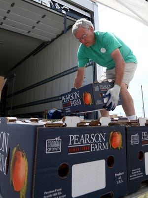 Nelson Piersey with the Georgia Peach Connection unloads 25-pound boxes of fresh Georgia Peaches at Belle Starr Antiques, 410 N. B., Friday, July 3, 2020, for pre-order pick-up and host site sales. Piersey said the peaches were harvested Tuesday, June 30, and since delivered throughout Northwest Arkansas with 70 boxes pre-ordered in Fort Smith.