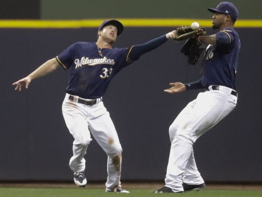 Milwaukee Brewers' Domingo Santana and Brett Phillips nearly collide as Phillips can't catch a ball hit by San Francisco Giants' Eduardo Nunez during the ninth inning of a baseball game Monday, June 5, 2017, in Milwaukee. The play was ruled an error. (AP Photo/Morry Gash)