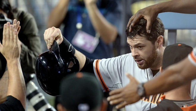 Brandon Belt is greeted in the dugout after scoring a run in the 13th inning.
