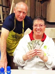 Bingo Committee member Bernie Seidman awards Anita Lawlor from Chicago her big winnings at JCMI's Monday Night Bingo.