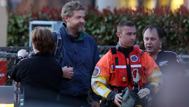 Louis Jordan, second from left, walks from the Coast Guard helicopter to the Sentara Norfolk General Hospital in Norfolk, Va., after being found off the coast, April 2, 2015. His family says he sailed out of a marina in Conway, S.C., on Jan. 23, and hadn't been heard from since.