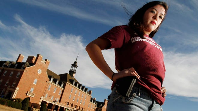 Adrienne O'Reilly, Oklahoma director for Students for Concealed Carry on Campus, carries an empty gun holster in 2011.
