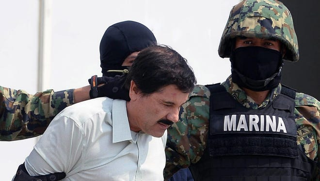 """Mexican drug trafficker Joaquin """"El Chapo"""" Guzman is escorted by marines as he is presented to the news media on Feb. 22, 2014, in Mexico City."""