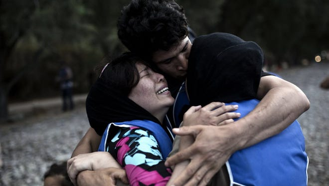 A migrant woman cries as she is embraced by a relative upon their arrival on the shores of the Greek island of Lesbos after crossing the Aegean Sea from Turkey on a dinghy on Sept. 10.