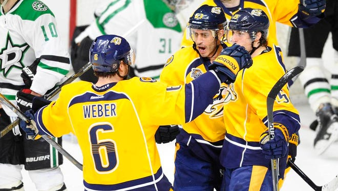 Predators center Mike Ribeiro (63) celebrates with right winger Craig Smith (15) and defenseman Shea Weber (6) after a goal during the first period against the Stars at Bridgestone Arena.