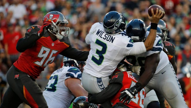 Buccaneers defensive end Ryan Russell (96) sacks Seahawks quarterback Russell Wilson (3) during the first half.