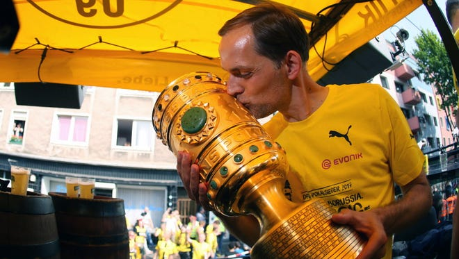 Thomas Tuchel kisses the trophy at Borsigplatz during celebrations after winning the German Cup final in Dortmund.