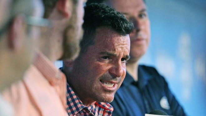 Miami Marlins President David Samson, center, speaks to members of the media before the start of a baseball game against the Colorado Rockies.
