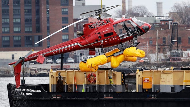 A helicopter is hoisted by crane March 12, 2018, from the East River onto a barge in New York after a crash that killed five people.
