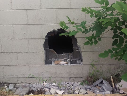 Outside view of a hole made in the wall to gain entry