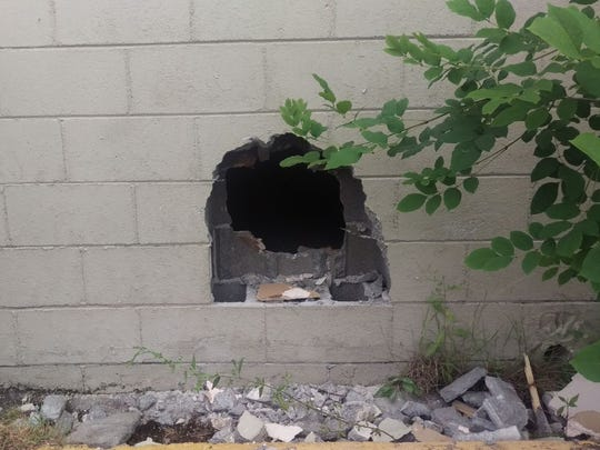 Outside view of a hole made in the wall to gain entry to Home Furniture in Montgomery.