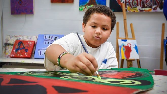 Jamil Abdille, 11, paints a replica of a Somali Bowdheer jar on cardboard Wednesday, Nov. 1, at the Southside Boys & Girls Clubs of Central Minnesota.