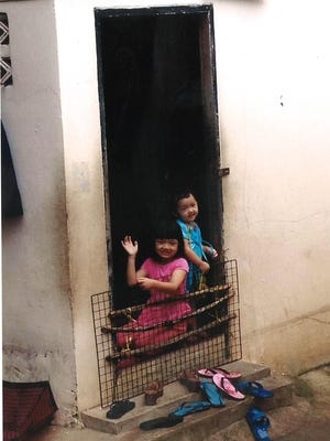 Children wave from a window in the slums of Thailand, where Behnke and other American women sought out victims of human trafficking.