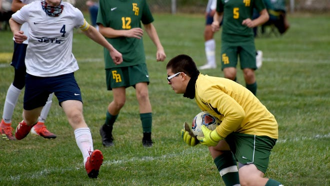 Oscar Gonzalez of Flat Rock makes a save as Airport's Noah Wolfenbarger looks for a rebound Monday, The teams played to a 1-1 tie.