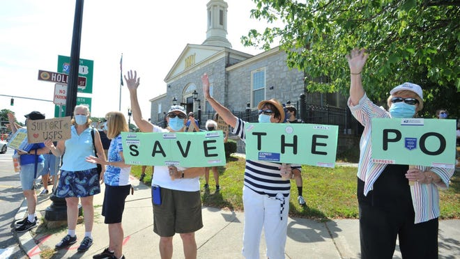 Protesters wave to passing motorists as they rally against recent cuts at the US Postal Service in front of the East Milton Post Office, Saturday, Aug. 22, 2020. Tom Gorman/For The Patriot Ledger