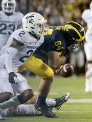 Michigan's Sean McKeon, right, fumbles the ball as