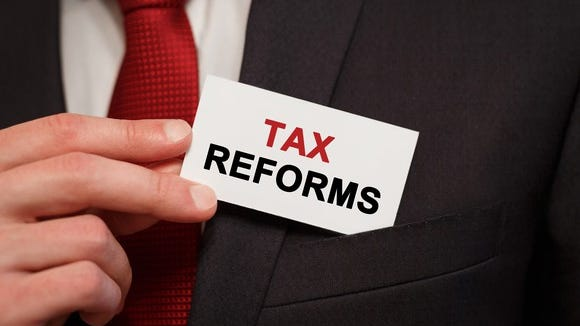 A man puts a business card in his pocket that reads tax reforms.