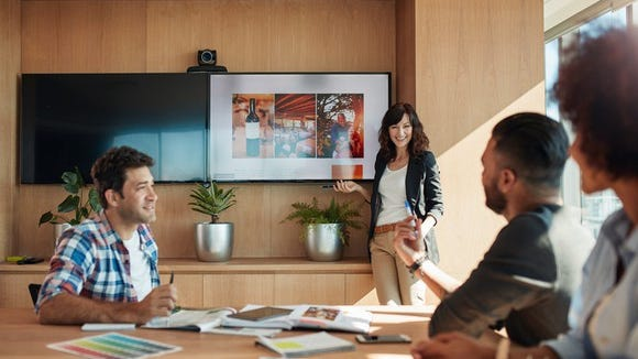 Female co-worker making presentation in contemporary office setting.
