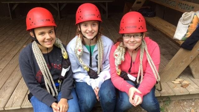 Sidonie Mangeot, of Edgewood, Maeve Dunn, of Walton, and Katie Moellman, of Foster, contemplate the zip line at Camp Joy.