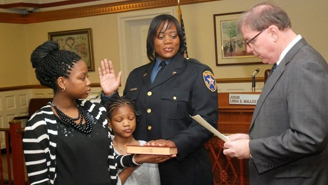 Veteran Sheriff's Officer Nakera Sherman is sworn in to her new rank of sergeant by Union County Sheriff Joe Cryan with the help of her daughters, Kayla (far left) and Jada.