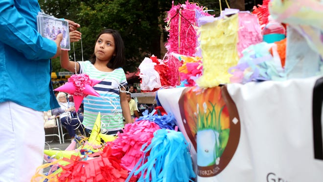 Piñatas sit on display at the Manantial Hispanic Support booth during the third annual Iowa City Latino Festival on Saturday, Aug. 16, 2014, in the pedestrian mall in downtown Iowa City.