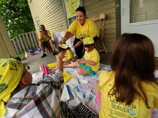 (From left) Members of the Miller family, Jacob, 11, father Josh, Jencyn, 6, mother Jennifer, Jillian, 5, and Jessika, 10, complete fliers for Alex's Lemonade Days at their 22nd Street home, Friday, June 12, 2015. Jillian is in remission after fighting leukemia for the past two years. The Miller family will host the lemonade stand fundraiser at their home Saturday to benefit children with cancer.