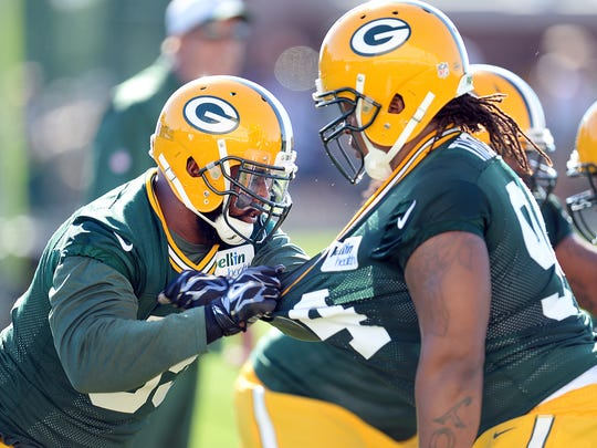 Defensive tackle Datone Jones (95), left, spars with lineman Khyri Thornton (94) during Green Bay Packers Training Camp at Ray Nitschke Field July 30, 2015.