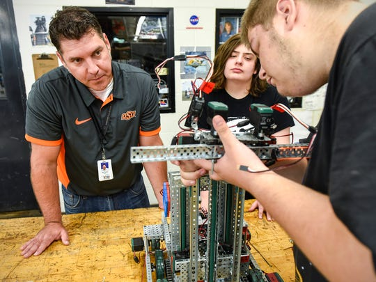 Teacher Matt Keil works with students Aiden Rieland and Zachary Gadient on their robotics project Wednesday, Sept. 12, at Technical High School.