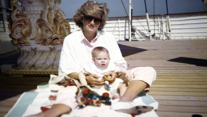 An undated handout picture released on July 22, 2017, by Kensington Palace from the personal photo album of Diana, Princess of Wales, shows the princess sitting and playing with Prince Harry on the Royal Yacht Britannia.