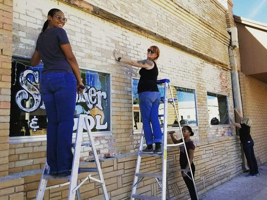 Volunteers work on the facade of Mission Billiards