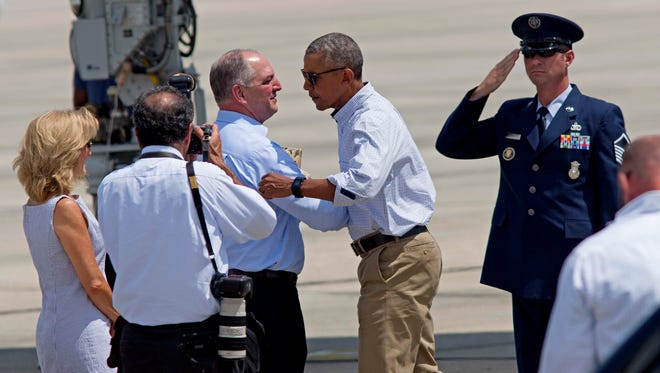 President Obama shakes hands with Louisiana Gov. John Bel Edwards after emerging from Air Force One at Baton Rouge Metropolitan Airport, Tuesday, prior to surveying the flood damaged region in Baton Rouge, La.