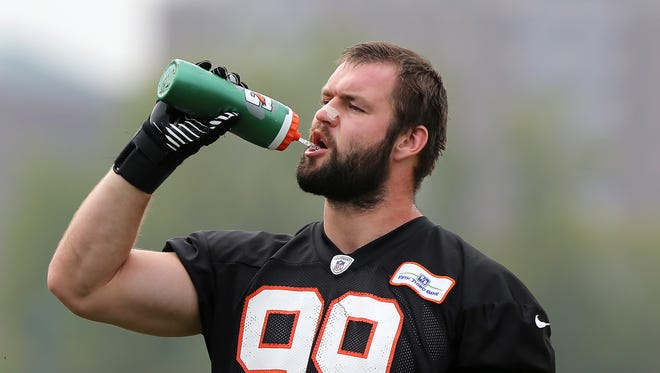 Margus Hunt takes a water break during Cincinnati Bengals training camp on the practice fields at Paul Brown Stadium.