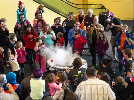 """Visitors gather for the """"Pie-plosion,"""" an exploding fake pie made of plastic balls, Saturday, March 14, 2015, as the Science Center of Iowa celebrates Pi day, which is observed on 3/14, since 3, 1 and 4 are the first three significant digits of pi in decimal form."""