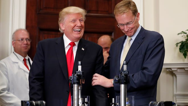 President Donald Trump, left, smiles with Wendell P. Weeks, chairman and chief executive officer of Corning Glass, during an event to announce a Merck, Pfizer, and Corning joint partnership making glass containers for medication, in the Roosevelt Room of the White House, Thursday, July 20, 2017, in Washington.