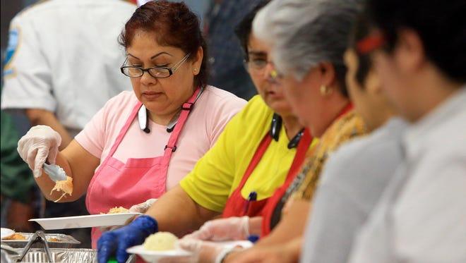 GABE HERNANDEZ/CALLER-TIMESVolunteer Maria Carrillo serves a plate of turkey during the Joe Salem Thanksgiving Dinner on Wednesday, Nov. 25, 2015, at the Boys and Girls Club in Corpus Christi.