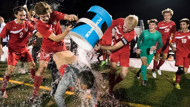 Susquhannock soccer head coach Brett Maxwell gets hit with the water cooler as the Warriors shut out Biglerville 6-0 to become YAIAA Champions on Thursday, Oct. 19, 2017.