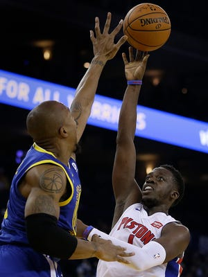 Pistons guard Reggie Jackson, right, shoots against Warriors forward David West during the first half of the Pistons' 115-107 win on Sunday in Oakland, Calif.