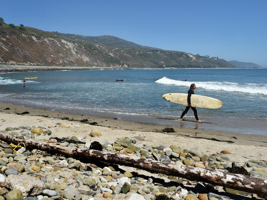 A surfer walks along the beach at Rincon Point on Wednesday.