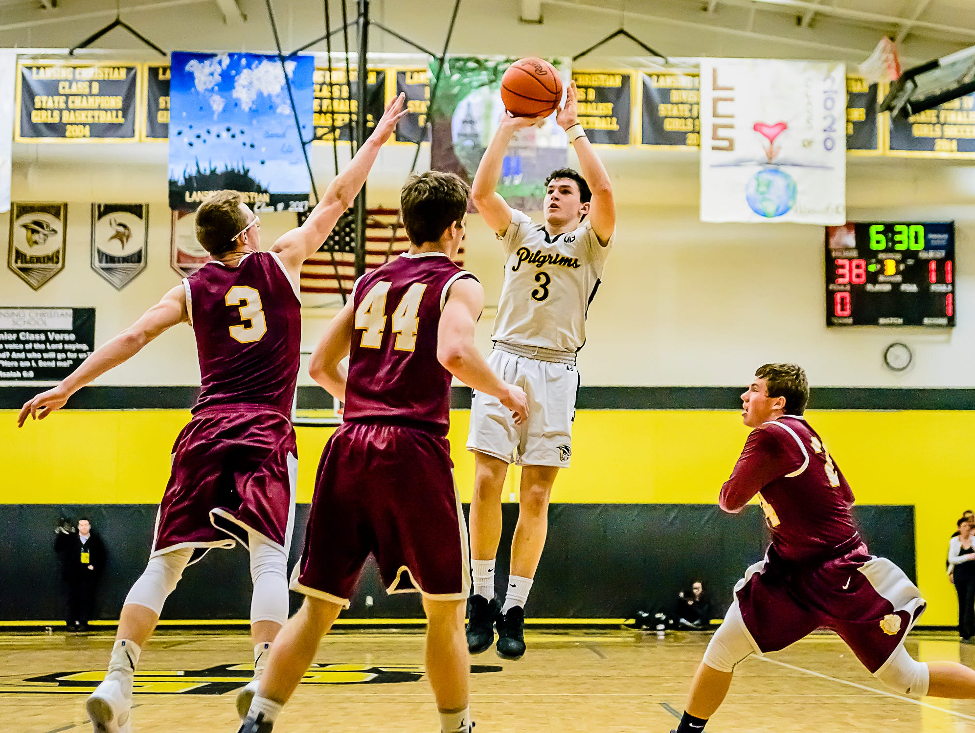 Matt Havey ,3, of Lansing Christian shoots over several Morenci defenders during their Class D regional semifinal Monday.
