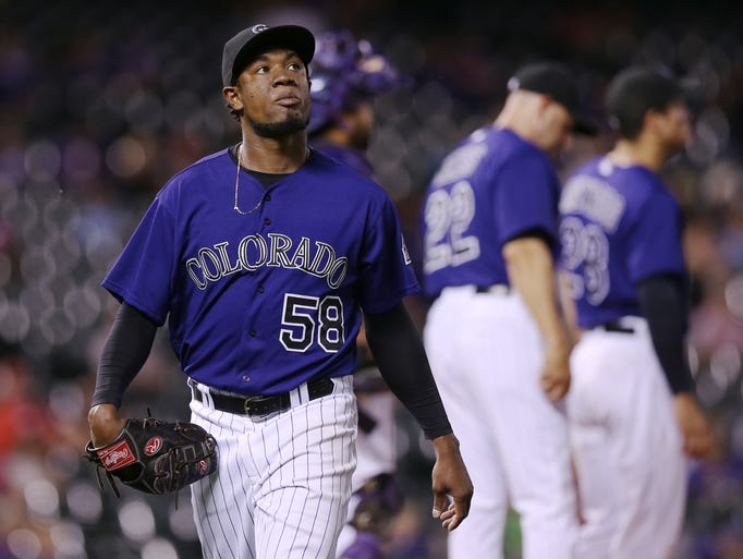 Colorado Rockies starting pitcher Yohan Flande, front, heads to the dugout after being removed from the mound after giving up an RBI-double to Cincinnati Reds' Brayan Pena in the sixth inning of a baseball game in Denver on Sunday, Aug. 17, 2014. The game is being made up after it was postponed on Saturday by a water main break that left the stadium waterless.