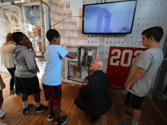 Retired New York City Firefighter Doug Guercia talks to students inside a trailer operated by the Stephen Siller Tunnel to Towers Foundation as it visits Albert Leonard Middle School in New Rochelle on Wednesday to educate students about Sept. 11, 2001.
