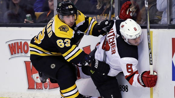 Boston Bruins left wing Brad Marchand (63) checks New Jersey Devils defenseman Will Butcher (8) into the boards during the second period of an NHL hockey game Tuesday, Jan. 23, 2018, in Boston.
