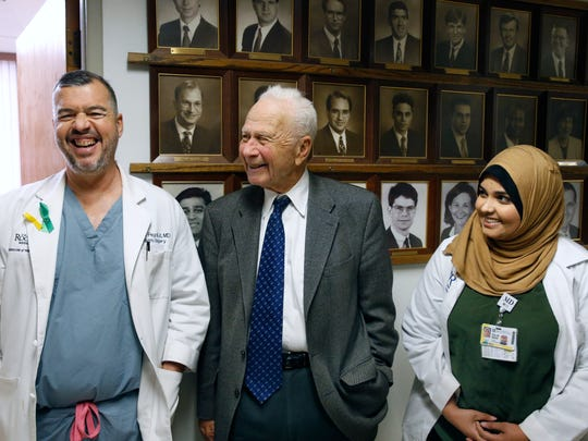 Dr. Seymour Schwartz, a URMC retired surgeon who turns 90 on Jan. 22, having some laughs with Dr. Walter Pegoli, chief of pediatric surgery and Pakistani surgery resident Dr. Elaa Mahdi, at Strong Memorial Hospital.
